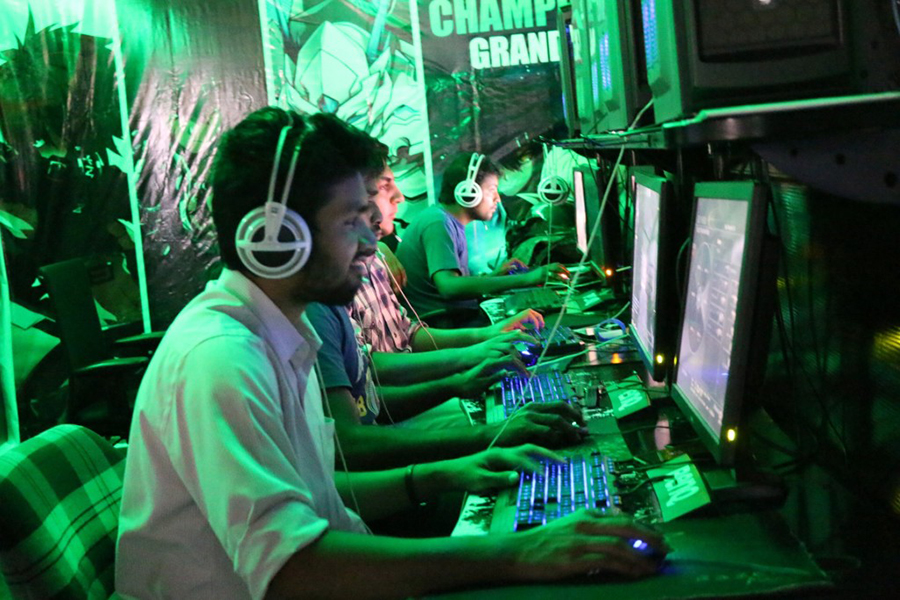 Only the glow from their monitors and computer towers illuminates the people playing games inside the League of Extraordinary Gamers. (Photo: Marvin Fuentes)