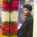 A flower garland merchant rests from stringing blossoms next to his completed product. (Photo: Rick Ricioppo)
