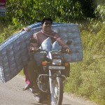 While the driver carries pillows on his lap, his passenger holds on to a mattress.  (Photo: Rick Ricioppo)
