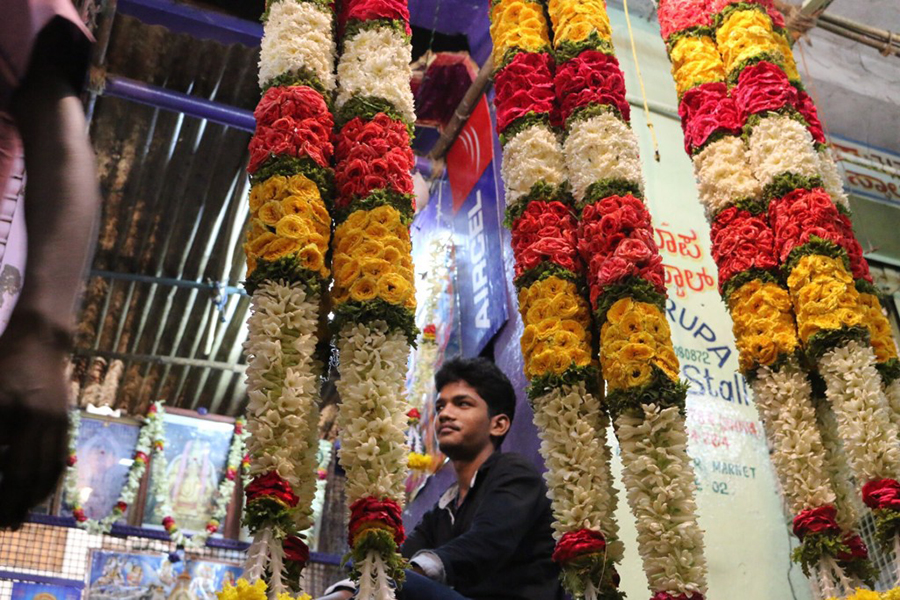 Inside City Market, workers like this man create elaborate flower garlands and arrangements to be sold fresh every day. (Photo: Marvin Fuentes)
