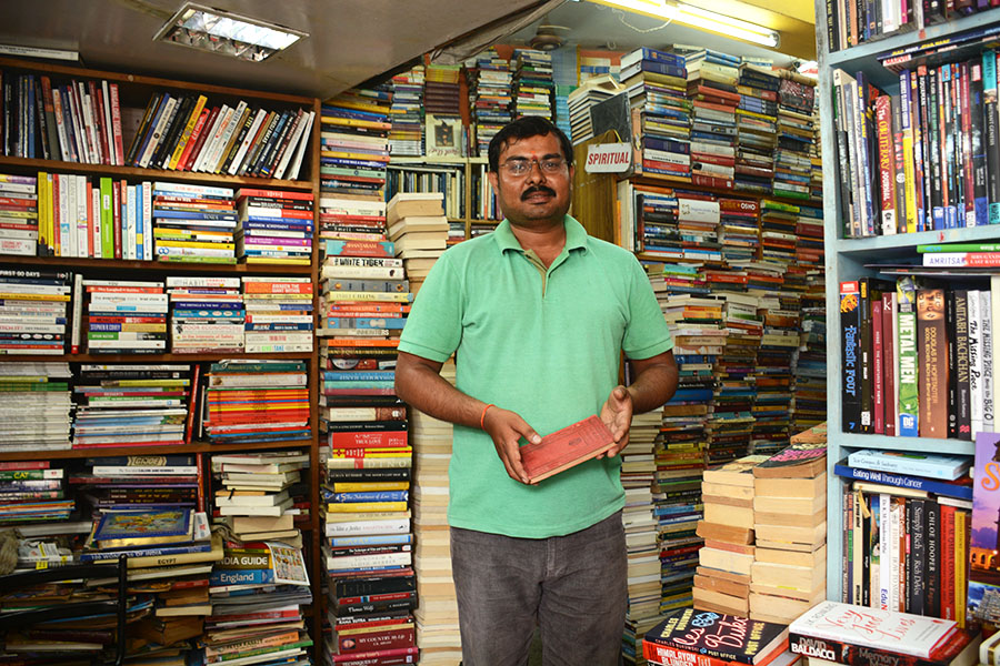 Krishna Gowda, owner of Bookworm, in front of the thousands of books in the secondary store location. (Photo: Kevin Matyi)