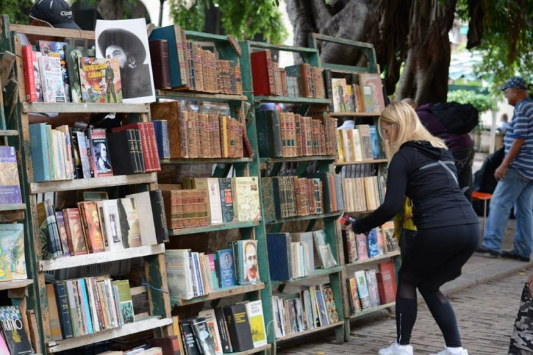 A student reaches down for a book from an outside stand in Old Havana. Photo by Janelle Clausen.
