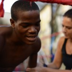Anna Somma massages Lisuan Lopez before a practice boxing match. Lopez, 20, started boxing at seven years old and now aside from fighting professionally, he trains young children how to box. Photo by Briana Lionetti