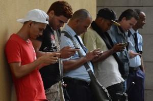 Cubans huddle up near a hotspot areas to get Wi-Fi connection. Photo by Emily Benson.