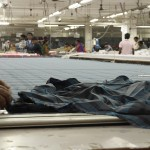 Workers prepare layers of fabric for cutting. (Photo: Krysten Massa)