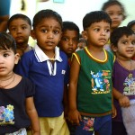 Factory workers' children and their teacher eye visitors at the company's crèche, or day-care center, at Indian Designs' Bangalore plant. (Photo: Alicia Bermudez)
