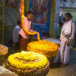 A merchant coils a length of garland as portraits of sacred figures look on benignly. (Photo: Rick Ricioppo)