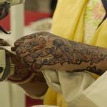 Henna-covered hands working on a sewing machine machine at Indian Designs. (Photo: Krysten Massa)