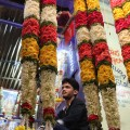 Below ground, workers like this man create elaborate flower garlands and arrangements to be sold at the market every day. (Photo: Marvin Fuentes)
