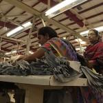 Two women sort pieces for assembling shirts. (Photo: Krysten Massa)