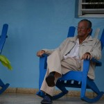 A man sits on his porch outside a casa particular. Photo by Janelle Clausen.