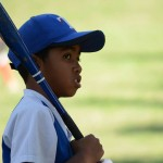 A young player looks to his coach for advice before stepping up to the plate. Photo by Janelle Clausen.