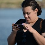 Abby looks through her phone for a good picture of the water. Photo by Janelle Clausen.